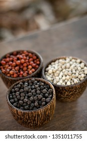 Organic kampot white red and black pepper corns in natural rustic style wood display in cambodia