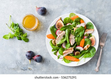Organic, kosher grilled chicken salad with figs, carrots, radish, spinach, and vinaigrette on a white plate and zinc surface.