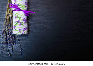 Organic Lavander Products with oil, lavander flower and towel on Wooden black table. Ingredients for Natural Spa Treatment