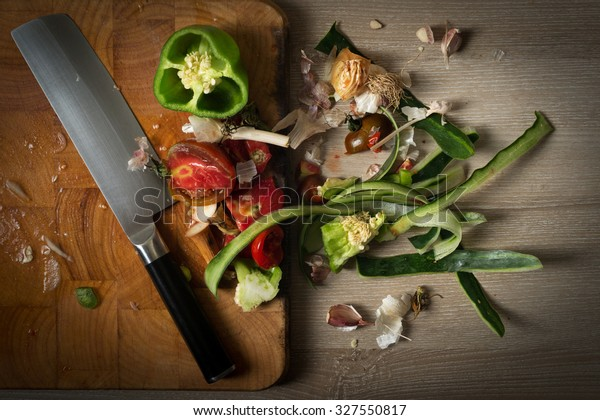 Organic leftovers ready for recycling and to compost,  waste from vegetable on top of wooden chopping board with japanese usuba kitchen knife.. Environmentally responsible behavior concept.