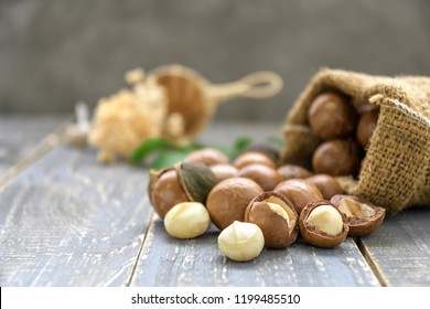Organic Macadamia nut on wooden table - vintage filter, Closeup view of natural macadamia oil and Macadamia nuts on wooden board. Healthy product