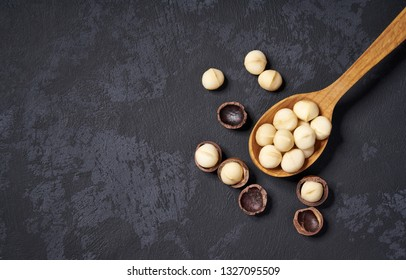 Organic macadamia nuts in wooden spoon on black table, with copy space. Healthy food.