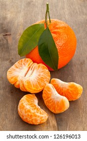 Organic mandarin whole and slices on wooden table