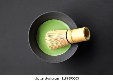 Organic matcha green tea in a Japanese ceramic tea cup with a bamboo tea whisk on black background
