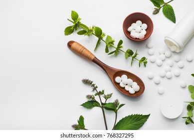 Organic medical pills with herbal plant on white background. ethnoscience concept. top view