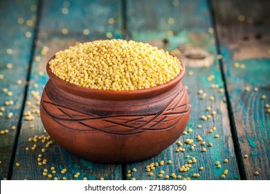 organic millet seeds in a ceramic bowl on wooden rustic table