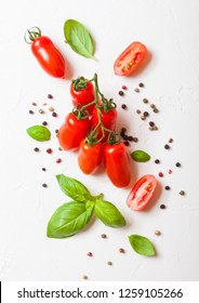 Organic Mini San Marzano Tomatoes on the Vine with basil and pepper on white background