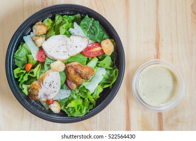 Organic mixed green salad with chicken in a transparent plastic plates on  wooden table very tasty
