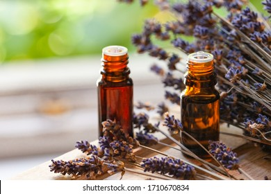 Organic natural essential lavender oil in small brown glass bottles. Dry flowers, green background. Concept of natural cosmetics. Faded colors, tonned in yellow. Close up, macro, copy space