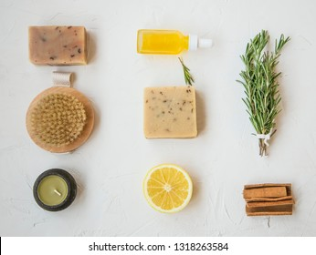 Organic natural skincare products flatlay with natural soap, oil bottle, brush, candle, rosemary herb, lemon and cinnamon, clean minimalist grey concrete background