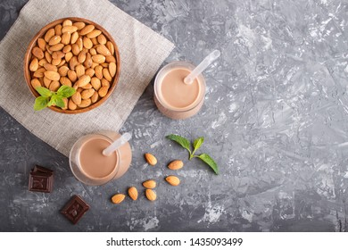 Organic non dairy almond chocolate milk in glass and wooden plate with almond nuts on a black concrete background. Vegan healthy food concept, flat lay, top view, copy space.