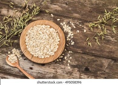 Organic oat flakes on a wooden plate.