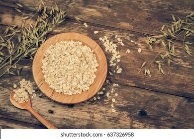 Organic oat flakes on a wooden plate. Vintage filtered and toned.
