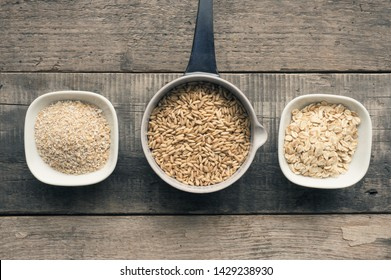 Organic oat grain, oat meal and oat bran on a rustic wooden kitchen table
