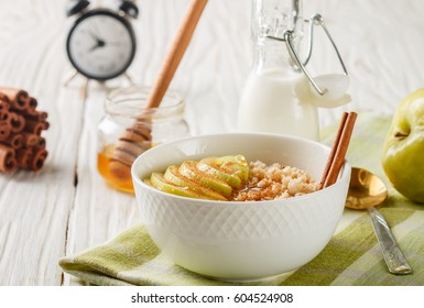 Organic oatmeal into a ceramic bowl with Apple, cinnamon and honey on white wooden table. Healthy Breakfast - the concept of proper nutrition and diet. Selective focus