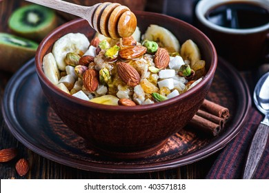 Organic oatmeal porridge with bananas, honey, almonds, pistachio, coconut, kiwi fruit, cinnamon, raisins in dark ceramic bowl  and cup of coffee. Healthy breakfast and diet concept on wooden table.
