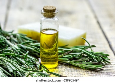 organic oil in bottle with soap, rosemary on light table background