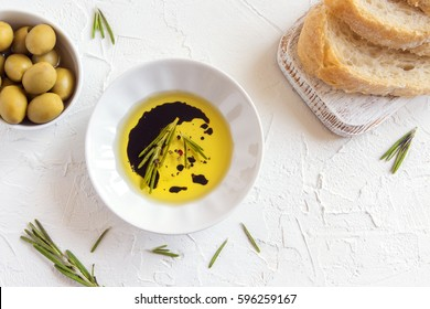 Organic olive oil with rosemary, balsamic vinegar and spices over white stone background with copy space, healthy food concept
