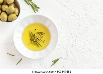 Organic olive oil with rosemary and spices (peppers) over white stone background with copy space, healthy food concept