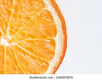 Organic orange segment with fresh vibrant colours and segmented into a single slice with a white background for health fruit based ideas and designs