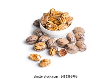 Organic pecan nuts on a white background, shelled and unshelled.
