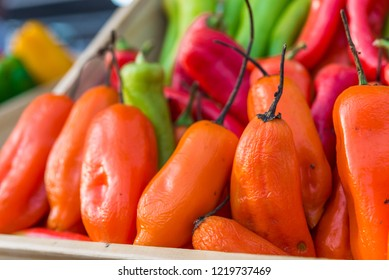 Organic Peruvian aji amarillo chili peppers on display in wooden boxes at a street food market fair festival