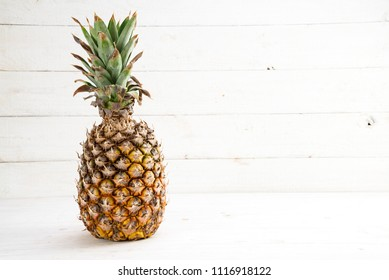 organic pineapple fruit on white painted wood, generous copy space