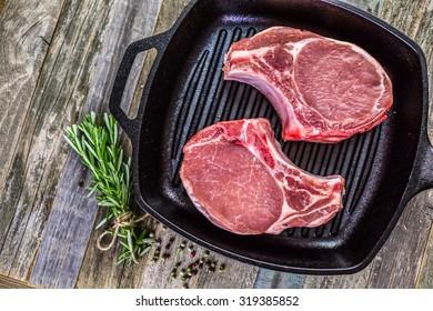 Organic pork lion chops of thick cut on cast iron frying pan.