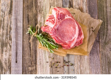 Organic pork lion chops of thick cut with rosemary.