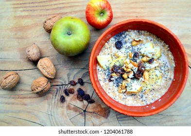 Organic porridge with oat flakes, fruit, raisins, nuts, chia seeds in rustic earthenware bowl. View from above on wooden background with ingredients: apples, raisins, nuts in shells. Healthy breakfast