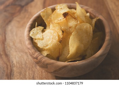 organic potato chips with herbs in bowl on wood table