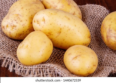 Organic potatoes on a jute bag. Potatoes from own cultivation. Potato growing. Potatoes as a component of dishes. Washed potatoes. Raw vegetables.