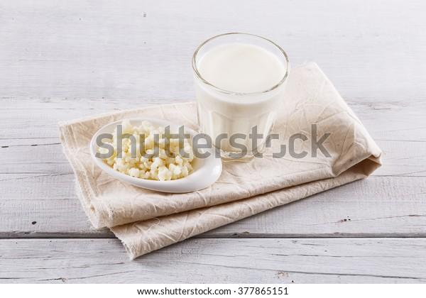 Organic probiotic kefir drink and kefir Tibetan mushrooms over white wooden background