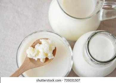 Organic probiotic milk kefir grains, Tibetan mushrooms on wooden spoon and kefir milk in glass containers