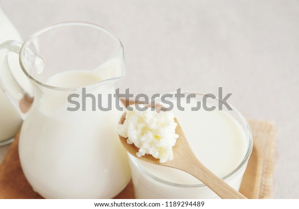 Organic probiotic milk kefir grains, Tibetan mushrooms on wooden spoon and kefir milk in glass containers, gut health