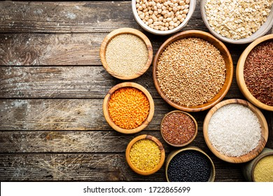 Organic products. Bowls with different gluten free grains on wooden background, top view
