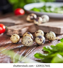 Organic quail eggs on an old wooden kitchen table with tomatoes and fresh greens. Healthy food