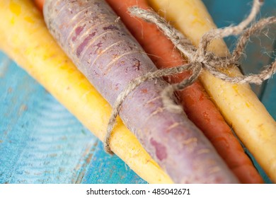 Organic Raw Carrots Bunch Tied Close Up On Colorful Blue Wood Texture Table Background. Selective Focus. Defocused.