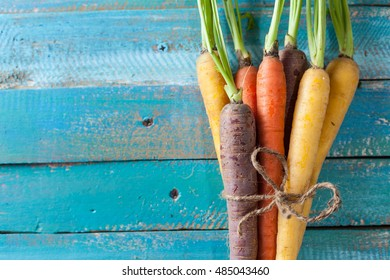 Organic Raw Carrots Bunch Tied On Colorful Blue Wood Texture Table Background. Selective Focus. Defocused. Copy Space.