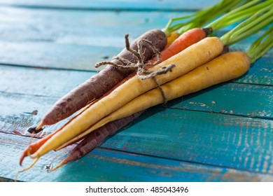 Organic Raw Carrots Bunch Tied On Colorful Blue Wood Texture Table Background. Selective Focus. Defocused.