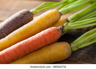 Organic Raw Carrots Close Up On Vintage Rustic Wood Texture Table Background. Selective Focus. Defocused.
