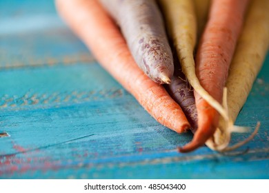 Organic Raw Carrots Close Up On Colorful Blue Wood Texture Table Background. Selective Focus. Defocused. Copy Space.