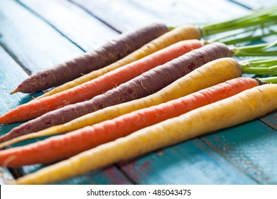 Organic Raw Carrots On Colorful Blue Wood Texture Table Background. Selective Focus. Defocused.