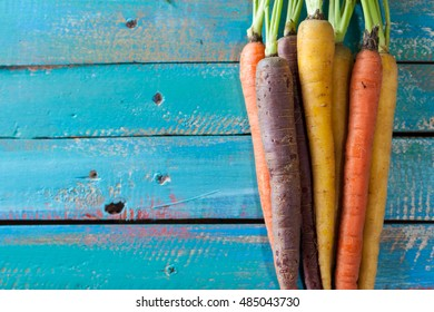 Organic Raw Carrots On Colorful Blue Wood Texture Table Background. Selective Focus. Defocused. Copy Space.
