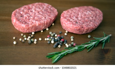 Organic Raw Ground Beef Meat Cutlet with Black and White and Red Peper and  Rosemary for Making Burger on Wooden Background Natural Light Selective Focus