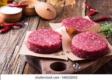 Organic raw ground beef, round patties for making homemade burger on wooden cutting board