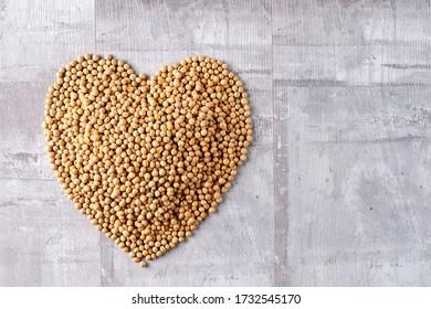 Organic raw vegan soy beans on wooden table arranged in heart shape
