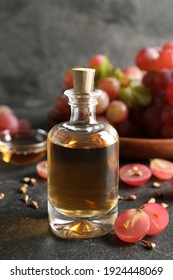 Organic red grapes, seeds and bottle of natural essential oil on black table