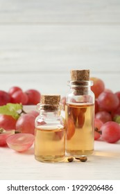 Organic red grapes, seeds and bottles of natural essential oil on white wooden table