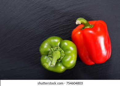 Organic red and green bell pepper on black slate stone plate with copy space